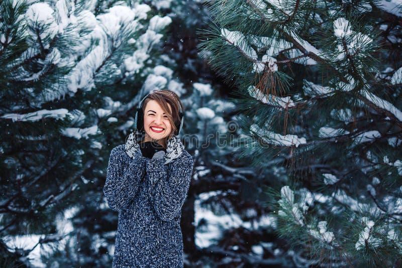 Modieus vrolijk meisje in een sweater in het de winterbos stock fotografie