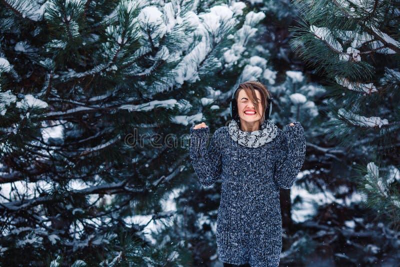 Modieus vrolijk meisje in een sweater in het de winterbos stock foto's
