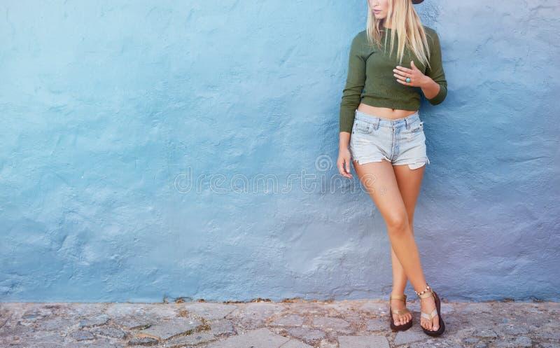 Modieus vrouwelijk model die zich tegen blauwe muur bevinden royalty-vrije stock afbeeldingen