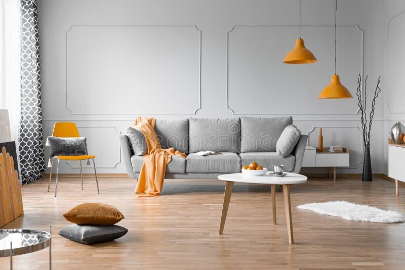 Modieus woonkamer binnenlands ontwerp met grijze laag, houten koffietafel en oranje accenten stock afbeeldingen