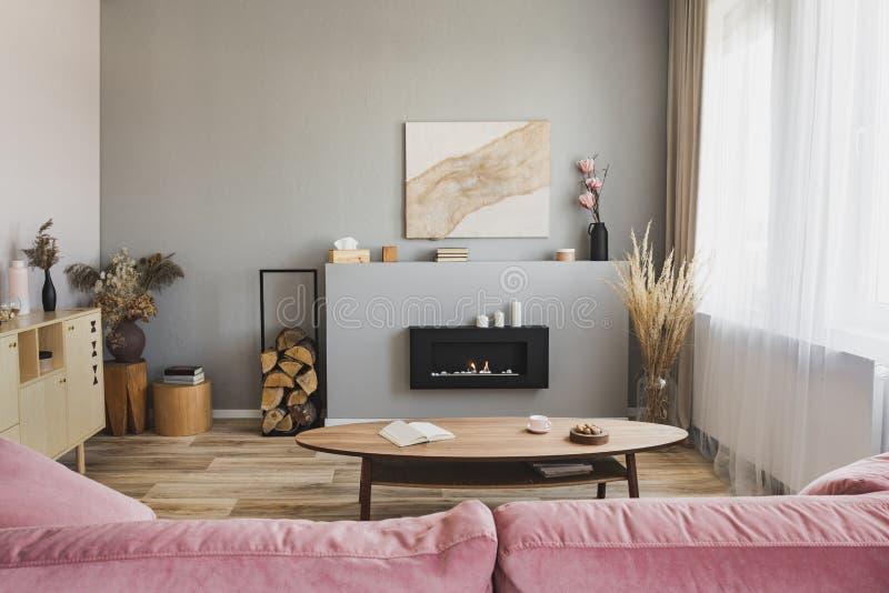 Modieus woonkamerbinnenland met pastelkleur roze bank, houten koffietafel en ecoopen haard royalty-vrije stock foto