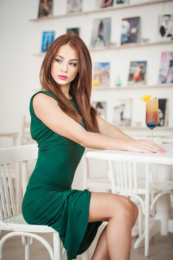 Modieuze aantrekkelijke jonge vrouw in groene kledingszitting in restaurant Het mooie roodharige stellen in elegant landschap met royalty-vrije stock afbeelding