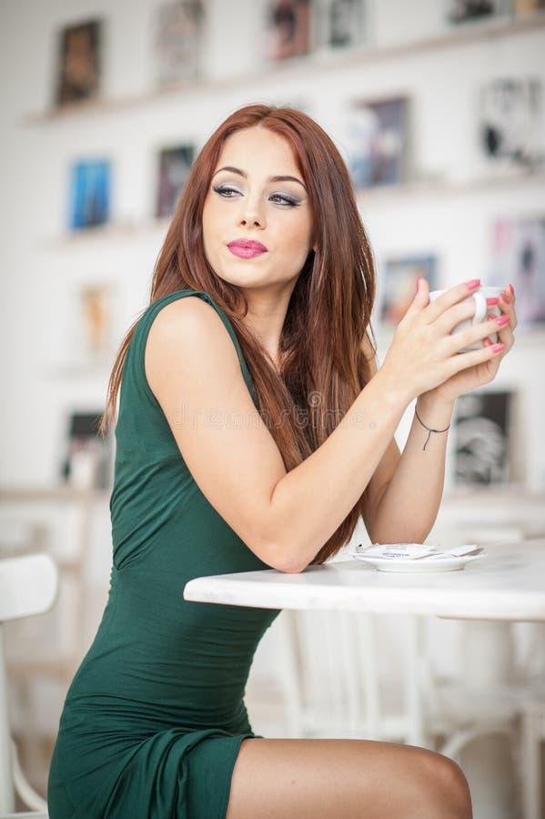 Modieuze aantrekkelijke jonge vrouw in groene kledingszitting in restaurant Het mooie roodharige stellen in elegant landschap met royalty-vrije stock fotografie