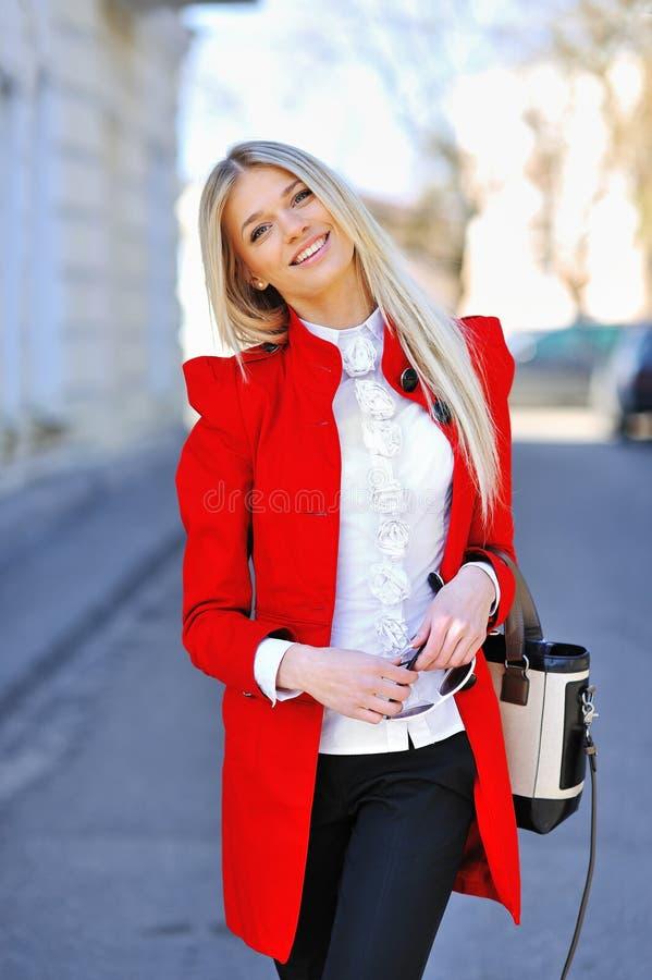 Modieuze aantrekkelijke yuongvrouw in rode kleding met zak royalty-vrije stock foto