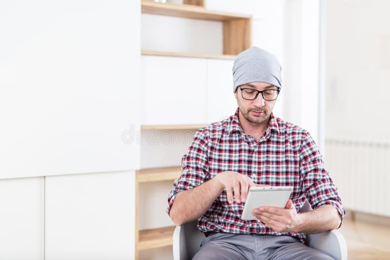 Modieuze architect of het uitvoerende apparaat van de holdingstablet op zijn kantoor stock afbeeldingen