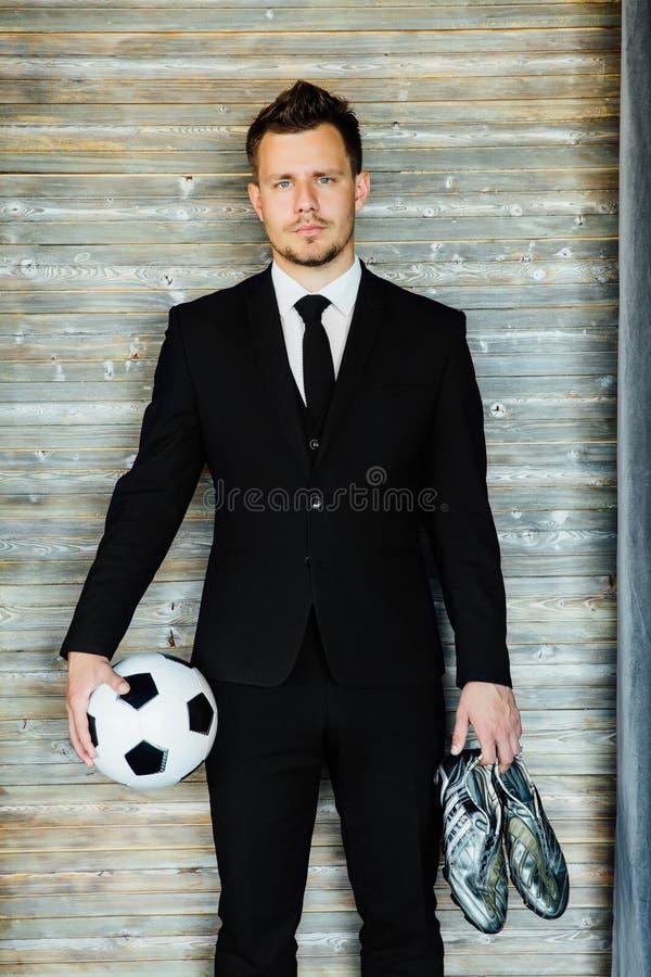 Modieuze atletische mens in een pak en een voetbalbal Tegen de achtergrond van een zoldermuur stock foto