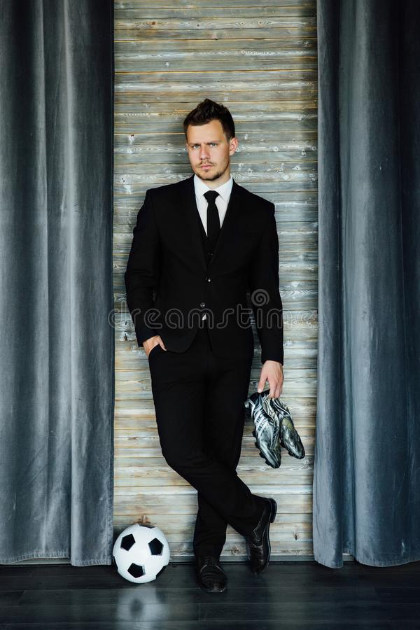 Modieuze atletische mens in een pak en een voetbalbal Tegen de achtergrond van een zoldermuur royalty-vrije stock afbeelding