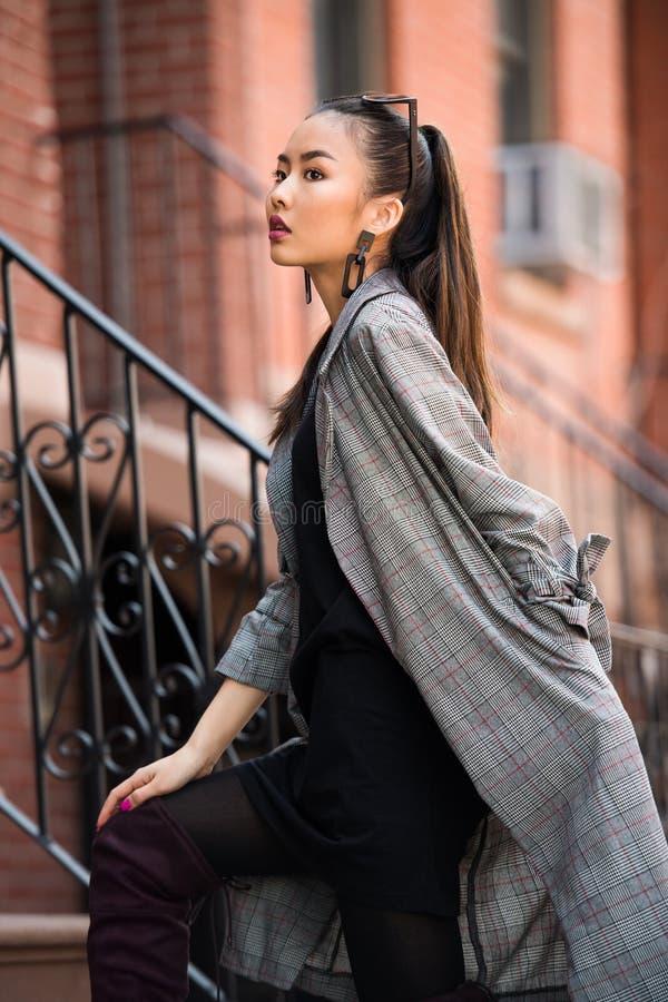 Modieuze Aziatische vrouw die modieuze de lenteuitrusting met grijs jasje en zwarte kleding dragen stock afbeelding