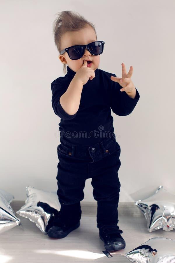 Modieuze babyjongen in zwarte tuimelschakelaarkleren en zonnebril royalty-vrije stock foto's