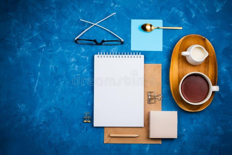 Modieuze bedrijfs flatlay model met notitieboekje, glazen, potlood, melkhouder en thee op houten dienblad stock foto