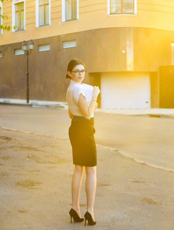 Modieuze bedrijfsvrouw die een spatie van document in haar handen houden en op de camera stellen het het werk proces stock foto's
