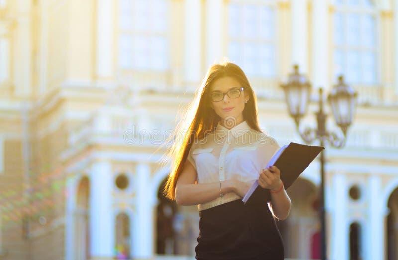 Modieuze bedrijfsvrouw die een spatie van document in haar handen houden en op de camera stellen het het werk proces Portret royalty-vrije stock foto