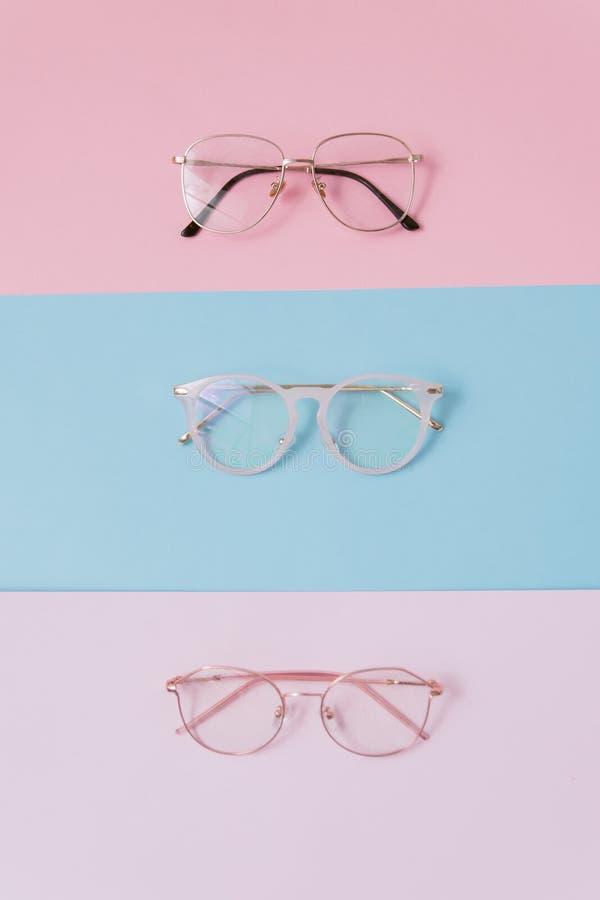 Modieuze beeldglazen op een pastelkleurachtergrond Drie paren glazen met lenzen op roze en blauwe achtergronden modieus en tenden royalty-vrije stock foto