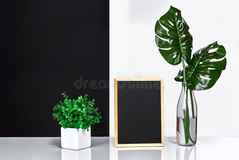 Modieuze binnenlands met spot op affichekader, bladeren in glasfles op lijst met zwart-witte muur op achtergrond stock fotografie