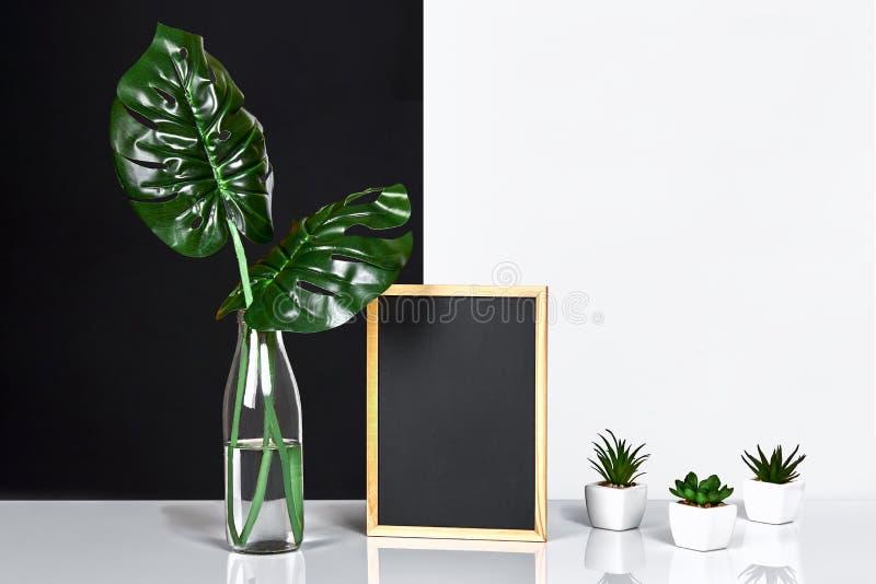 Modieuze binnenlands met spot op affichekader, bladeren in glasfles op lijst met zwart-witte muur op achtergrond royalty-vrije stock afbeeldingen