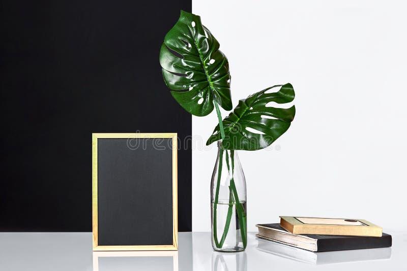 Modieuze binnenlands met spot op affichekader, bladeren in glasfles op lijst met zwart-witte muur op achtergrond stock afbeelding