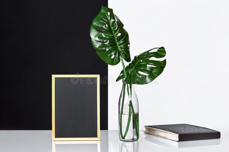 Modieuze binnenlands met spot op affichekader, bladeren in glasfles op lijst met zwart-witte muur op achtergrond royalty-vrije stock foto