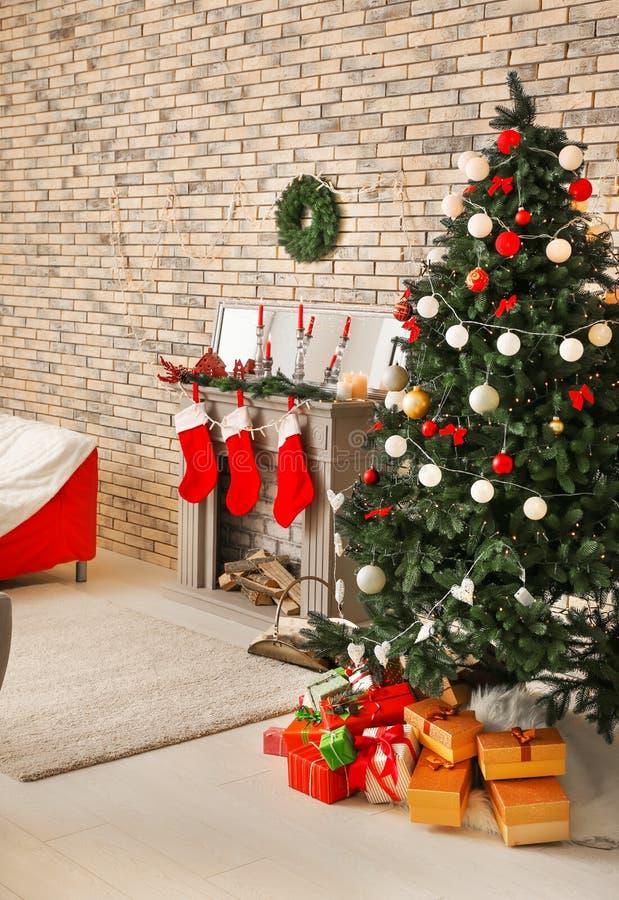 Modieuze binnenlands van ruimte met mooie Kerstmisspar en decoratieve open haard stock foto