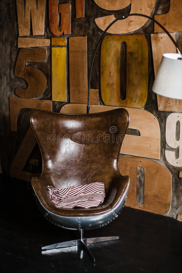 Modieuze binnenlands in zolderstijl grijs geweven pleister op de muur houten brieven comfortabele die leunstoel van bruin leer wo stock afbeelding