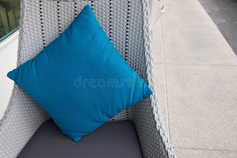 Modieuze blauwe kussens die rotanbank verfraaien stock afbeelding