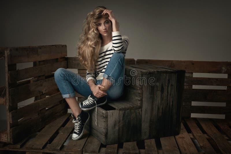 Modieuze blonde jonge meisjeszitting op een houten borst stock fotografie