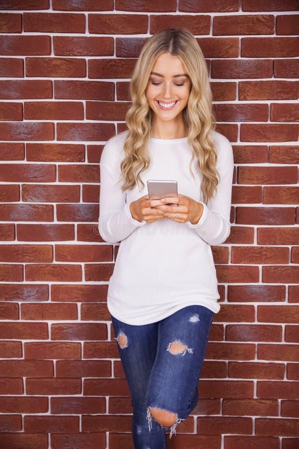 Modieuze blondevrouw die en smartphone glimlachen gebruiken royalty-vrije stock fotografie