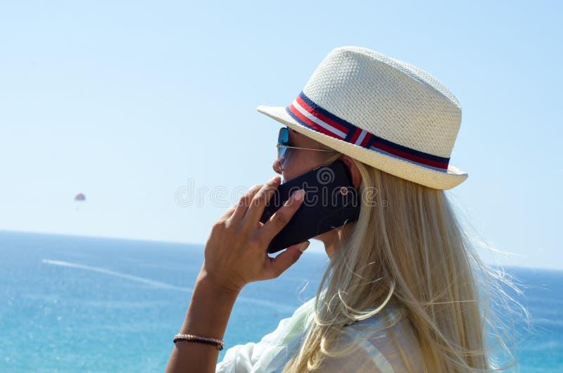 Modieuze blondevrouw die en smartphone glimlachen gebruiken royalty-vrije stock afbeelding