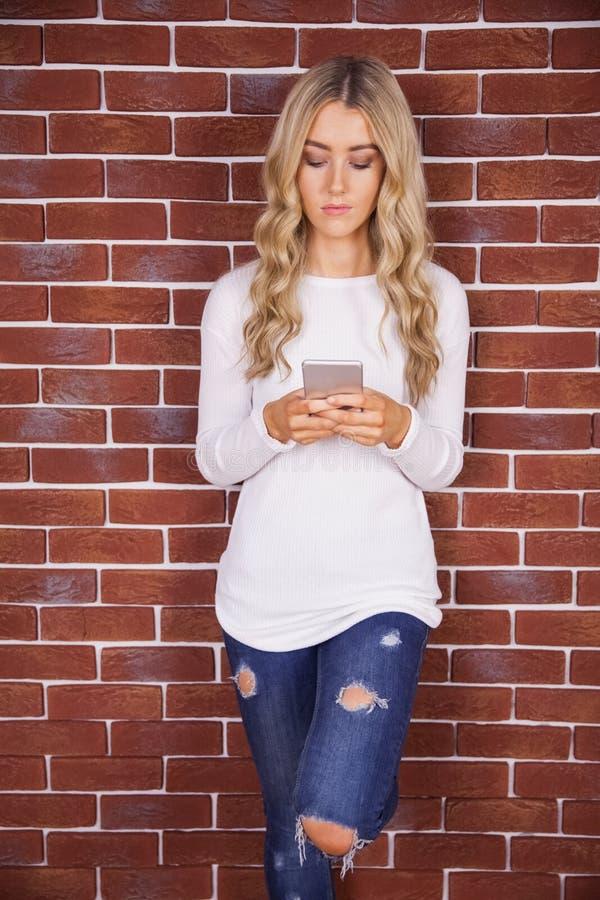 Modieuze blondevrouw die smartphone gebruiken royalty-vrije stock foto's