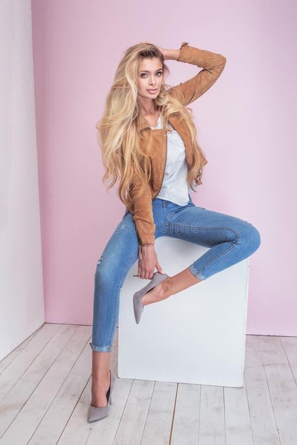Modieuze blondevrouw op roze achtergrond royalty-vrije stock fotografie