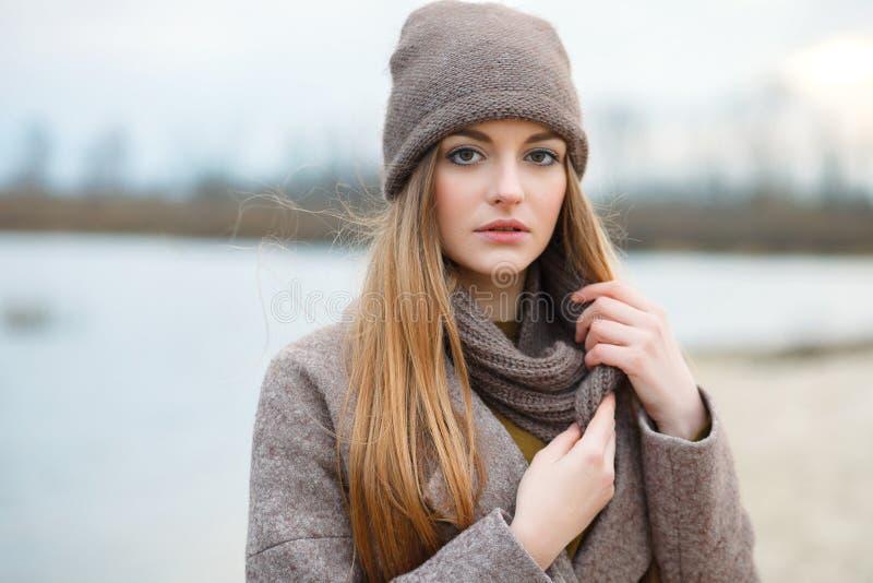 Modieuze blondevrouw in in stedelijk outwear stellend koud weer op de rivierbank Uitstekende filterfilm verzadigde kleur Dalingss stock fotografie