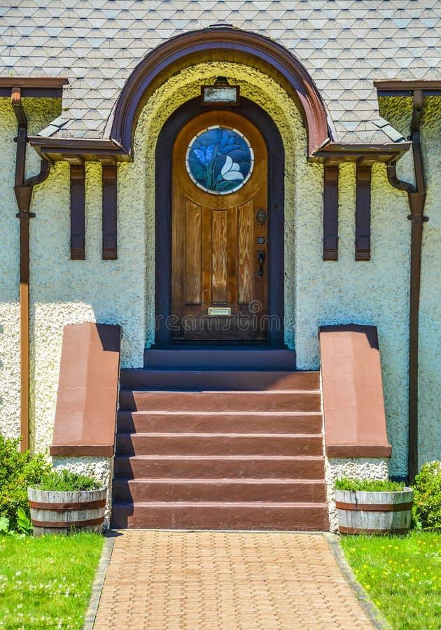 Modieuze boog buitendeur, houten deur van een huis met de secties van het mozaïekglas stock fotografie