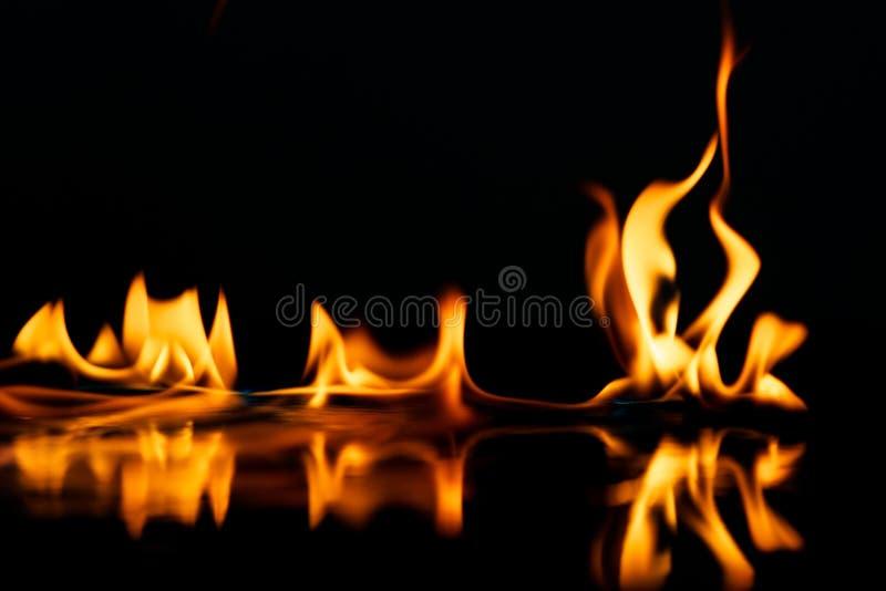 Modieuze brandvlammen die in water worden weerspiegeld stock afbeeldingen