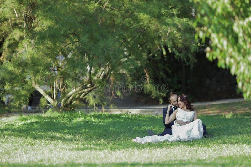 Modieuze bruid en bruidegom bij een park op hun huwelijksdag Mooi liefdeverhaal in aard, paar in liefde royalty-vrije stock fotografie