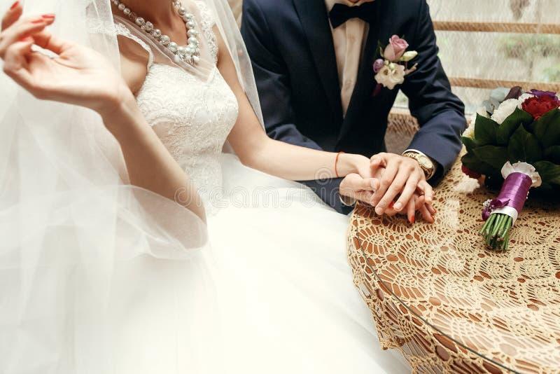 Modieuze bruid en bruidegomholdingshanden, zitting bij houten wijnoogst stock afbeeldingen