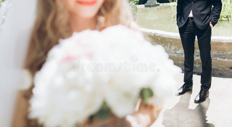 Modieuze bruid met pioenboeket en bruidegom in kostuum het stellen in zon royalty-vrije stock foto's