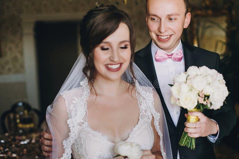 Modieuze bruidegom die met huwelijksboeket aan zijn schitterende bruid in verbazende toga met witte pioen boutonniere in handen e royalty-vrije stock foto's