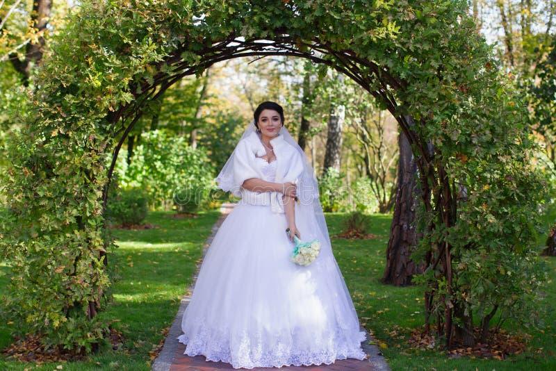 Modieuze bruidtribunes onder een groene boog royalty-vrije stock fotografie
