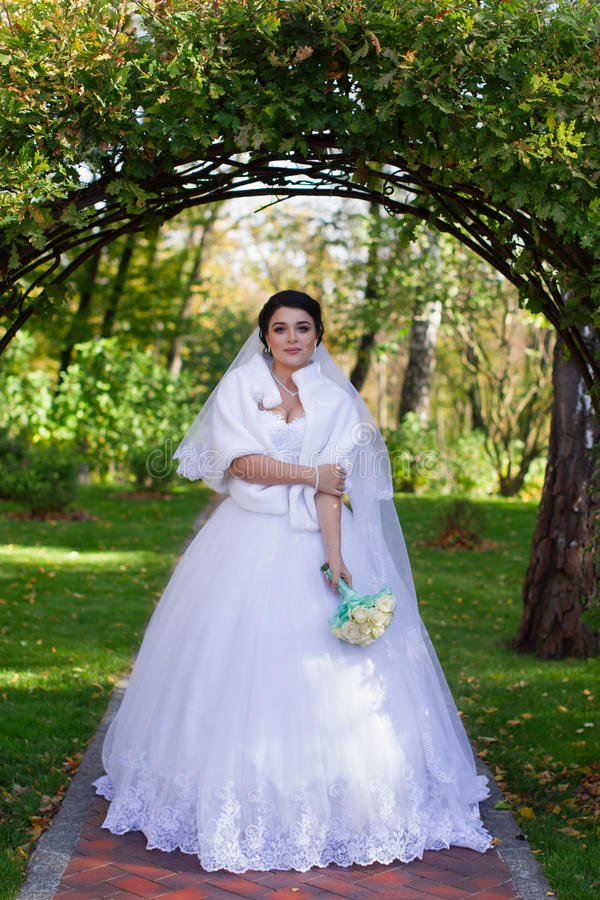 Modieuze bruidtribunes onder een groene boog royalty-vrije stock afbeelding