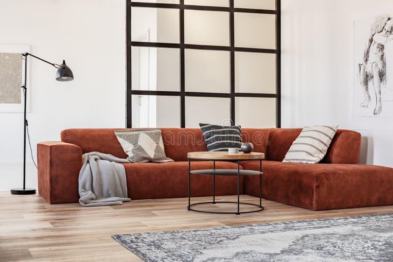 Modieuze bruine hoekbank met gevormde hoofdkussens in elegant woonkamerbinnenland met verticale raamstijlenmuur stock foto's