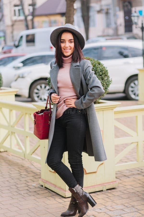 Modieuze charmante jonge vrouw die in grijze laag, hoed met rode zak op straat in stadscentrum lopen Donkerbruin elegant haar, stock foto
