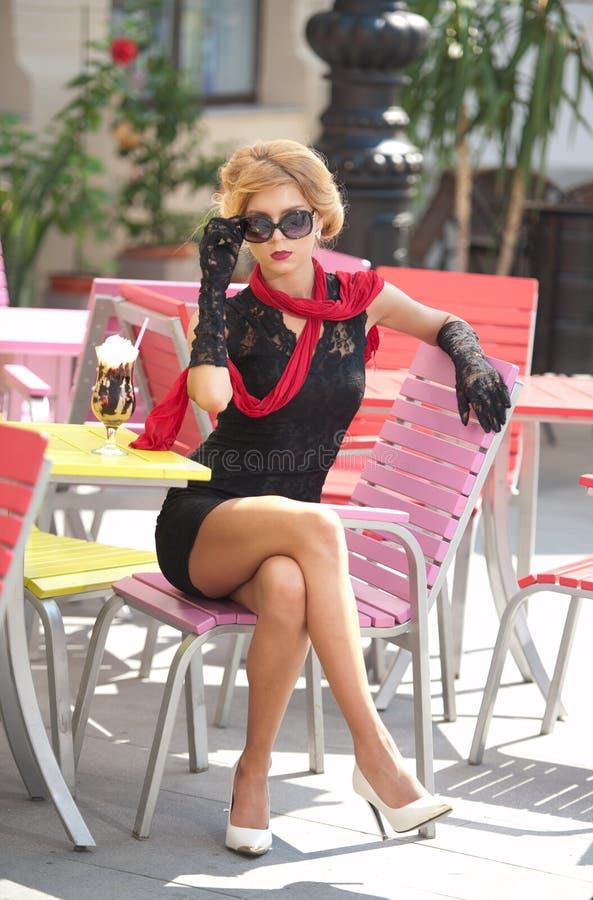 Modieuze dame met weinig zwarte kleding en rode sjaalzitting op stoel in restaurant, openluchtschot in zonnige dag Jong blonde royalty-vrije stock fotografie