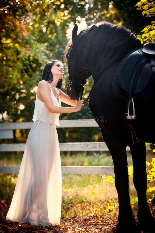 Modieuze dame met witte bruids kleding dichtbij bruin paard in aard Mooie jonge vrouw in het lange kleding stellen met een paard stock foto's