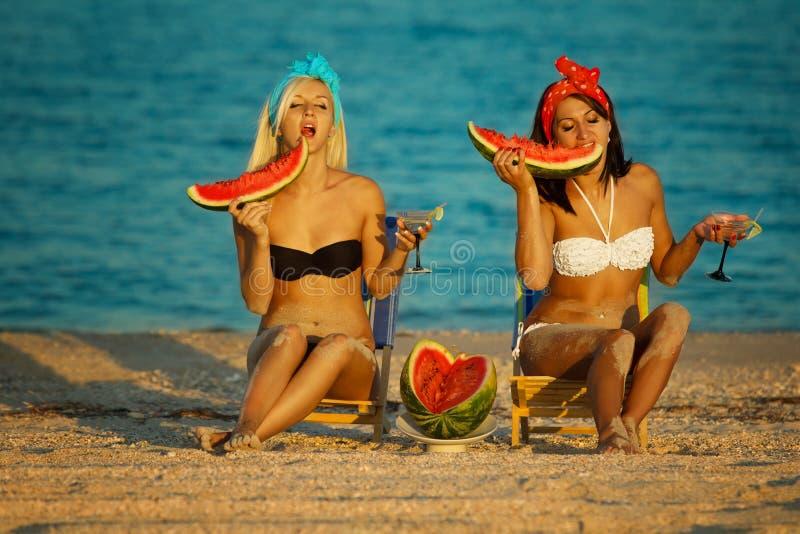 Modieuze dames op zee met watermeloen stock afbeeldingen