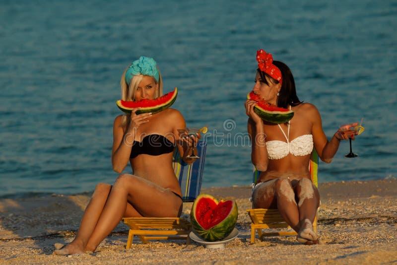 Modieuze dames op zee met watermeloen stock foto's
