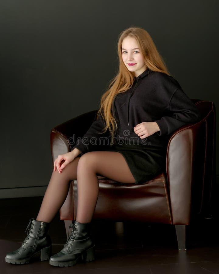 Modieuze de studiofoto van de meisjestiener op een zwarte achtergrond stock fotografie