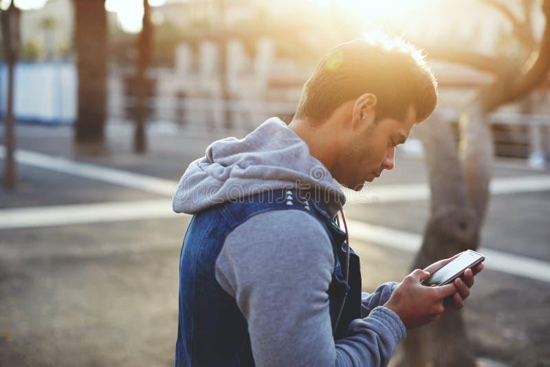 Modieuze donkerbruin hipster gebruikend celtelefoon bij zonnige avond royalty-vrije stock foto