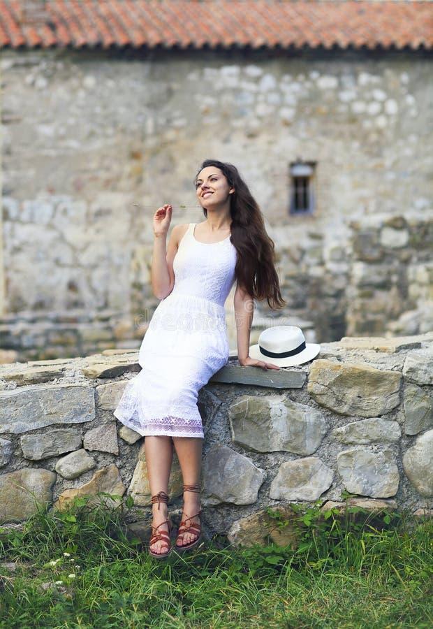 Modieuze donkerbruine vrouw in witte kleding op achtergrond van baksteen wal stock afbeeldingen