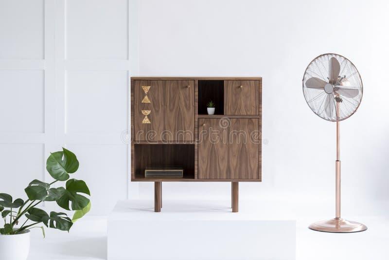 Modieuze donkere houten ladenkast in helder binnenland met groene installatie en koperventilator royalty-vrije stock afbeeldingen