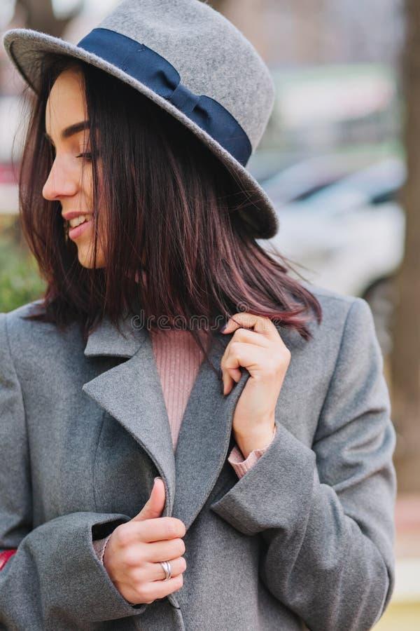 Modieuze elegante beeld blije jonge vrouw die met donkerbruin haar in grijze laag aan kant op straat glimlachen Luxelaag stock fotografie