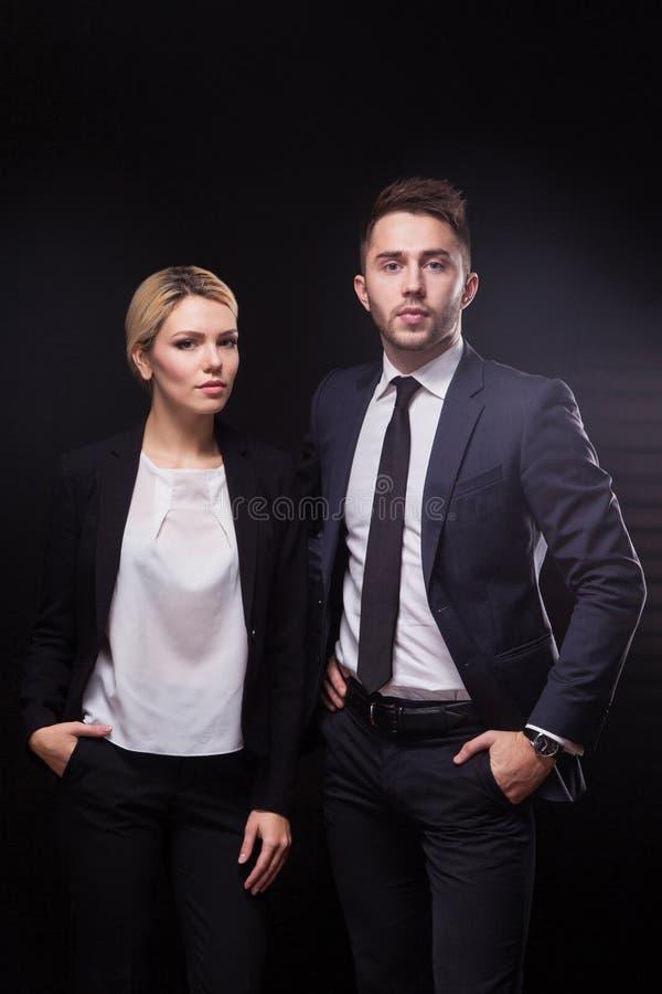 Modieuze, in en moderne bedrijfsman en vrouw op zwarte backg stock afbeeldingen